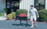 Man standing next to REC TEC Grills Mini Portable Pellet Grill