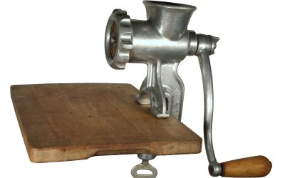 meat grinder on a wooden cutting board.