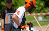 Guy Chainsawing in full protection gear